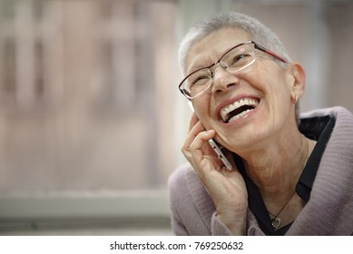 Smiling senior elderly lady having a pleasant conversation over her cell phone