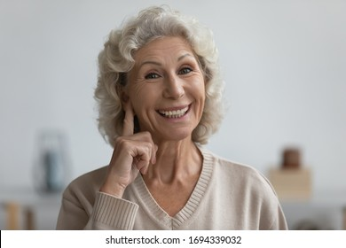 Smiling senior elderly woman looking at camera, showing on ear, having trouble with hearing, asking speaking louder. Head shot close up portrait happy middle aged grandmother with health disability.