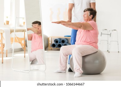 Smiling senior exercising with a physiotherapist on a silver ball at a white gym