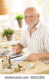 Smiling senior at financial activity at home, looking at camera.?