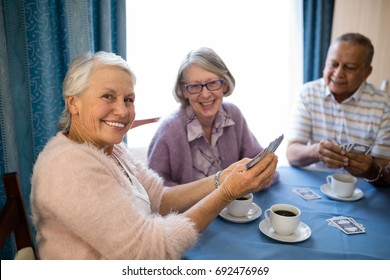 Smiling senior friends playing cards while having coffee at table in nursing home