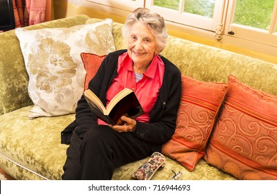 Smiling Senior, grey-haired woman, reading in her sitting room, in front of windows onto garden