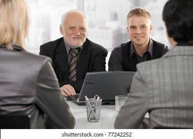 Smiling senior and junior businessmen sitting at meeting with businesswomen.?