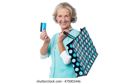 Smiling senior lady posing with credit card and shopping bag.