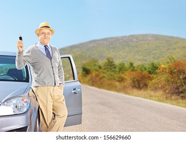Smiling senior male holding a car key next to his automobile on an open road, shot with a tilt and shift lens