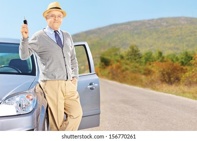 Smiling senior male holding a car key next to his automobile on an open road