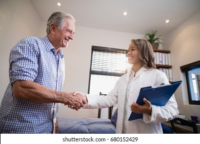 Smiling senior male patient and female therapist shaking hands at hospital ward