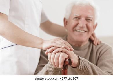 Smiling senior man and assisting helpful nurse