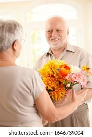 Smiling senior man bringing flowers to older woman.