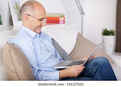 Smiling senior man browsing the internet in the living room