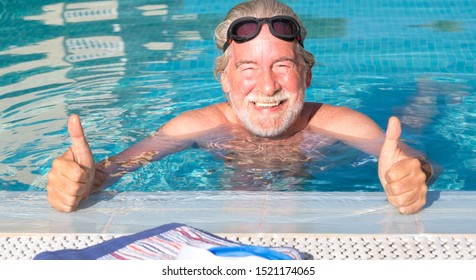 A smiling senior man doing sport and swimming in the blue swimming pool. Sun on the face. Man with white beard and mustache happy with his swim. Healthy lifestyle for a pensioner.
