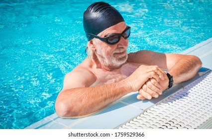 A smiling senior man doing sport in the outdoor swimming pool checking the time of the swim. Black swim cap and goggles. Concept of active elderly people during retirement