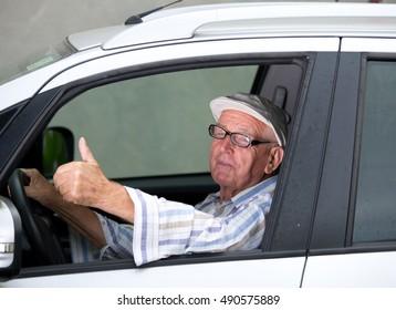 Smiling senior man driving car and showing ok sign