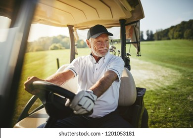 Smiling senior man driving a golf cart along a course while enjoying a round of golf on a sunny day