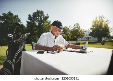Smiling senior man enjoying a coffee and reading a newspaper while relaxing at a course restaurant after playing a round of golf