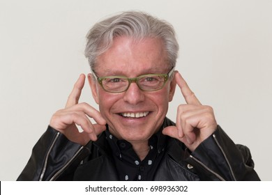 Smiling senior man with grey hair touching his green eyeglasses with index fingers