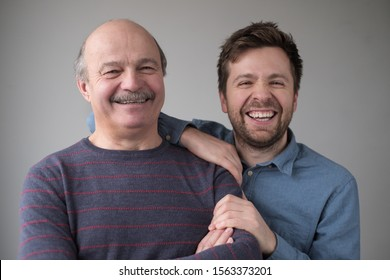 Smiling senior man with his grown up son smiling having positive mood. Stay close to your parent concept.
