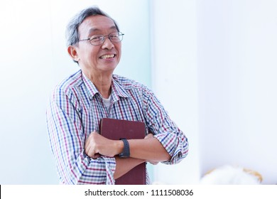 Smiling senior man holding book in home residence. Happiness retire male successful in good wealth and health.