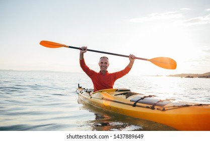 Smiling senior man in kayak holds paddles high. Active vacation, kayaking, paddling, canoeing