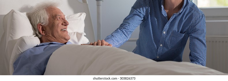 Smiling senior man lying in hospital bed