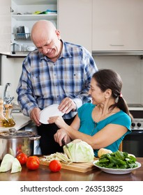 Smiling senior man and mature  woman cooking lunch together