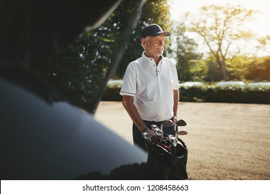 Smiling senior man packing his clubs into the trunk of his car after playing a round of golf on a sunny afternoon
