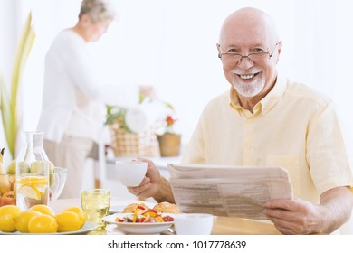 Smiling senior man reading a newspaper and drinking tea in the morning