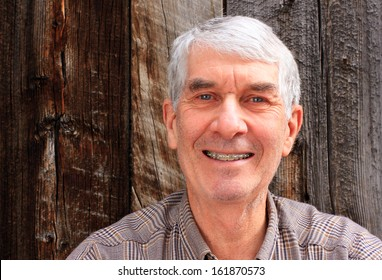 Smiling senior man with a rustic wood background.
