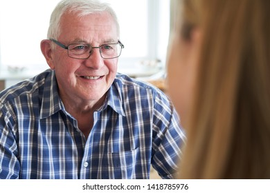 Smiling Senior Man Sitting In Kitchen Talking With Woman At Home