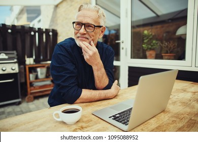 Smiling senior man sitting at a table outside on his patio working online with a laptop and drinking a cup of coffee