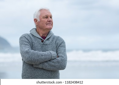 Smiling senior man standing with arms crossed on the beach