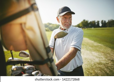 Smiling senior man standing by a golf cart looking out at the fairway while playing a round of golf on a sunny day