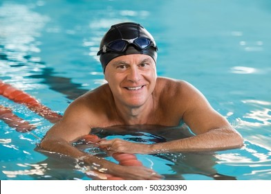 Smiling senior man standing in pool holding rope. Portrait of mature man wearing swim cap and goggles looking at camera. Proud and active retired man in swimming pool.
