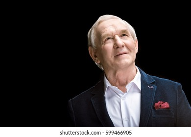 Smiling senior man in suit jacket looking up isolated on black
