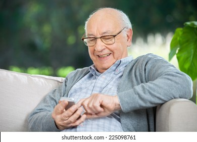 Smiling senior man text messaging through mobile phone at nursing home porch
