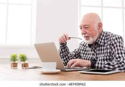 Smiling senior man using laptop, sitting at desk at home, copy space