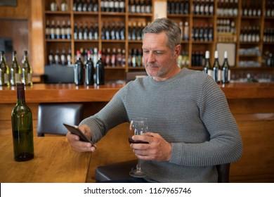 Smiling senior man using mobile phone while having red wine in restaurant