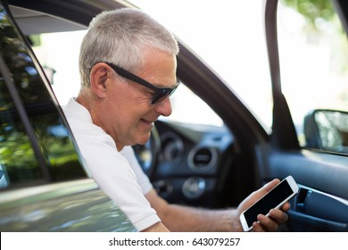 Smiling senior man using smart phone while sitting in car