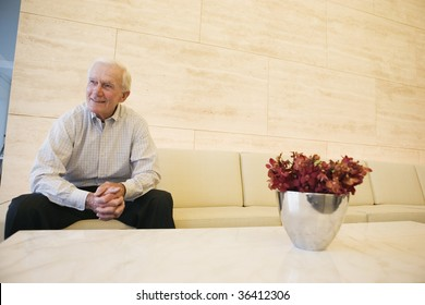 Smiling senior man waiting patiently in an office lobby.