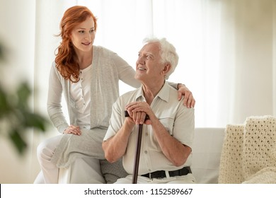 Smiling senior man with walking stick and his happy granddaughter at home