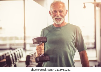 Smiling senior man with weight at gym. Looking at camera.