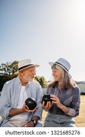 Smiling senior man and woman sitting together in a park and talking holding boules. Happy elderly couple wearing hats enjoying their time sitting in a boules park on a sunny day.
