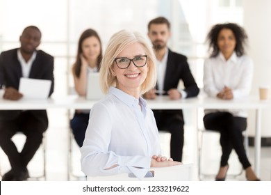 Smiling senior mature woman job applicant looks at camera at interview with hr recruiting team, happy middle aged lady business coach or vacancy candidate portrait, getting hired, employment concept