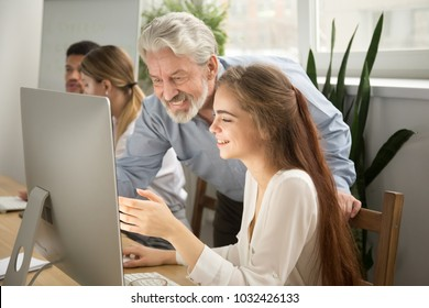 Smiling senior mentor supporting young intern showing achievement result online on computer screen, happy cheerful female employee talking to boss supervisor excited to tell executive good funny news
