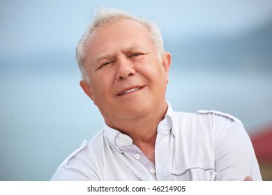 smiling senior near seacoast, inclined head aside