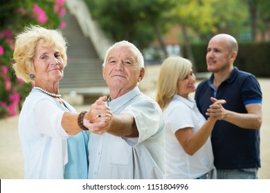 Smiling senior parents with adult children dancing in summer park