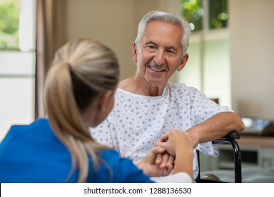 Smiling senior patient sitting on wheelchair with nurse holding hand. Old disabled man listening to doctor with a smiling face. Caring medical nurse comforting patient at home while holding hands.