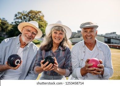 Smiling senior people sitting in a lawn holding boules. Two senior men and a woman enjoying the game of boules sitting together in a park.