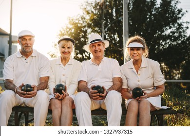 Smiling senior persons sitting in a park holding boules in their hands. Cheerful senior men and women sitting outdoors enjoying the game of boules.