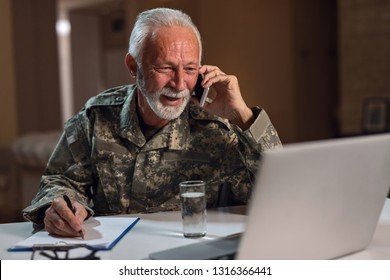 Smiling senior sergeant communicating on mobile phone while doing paperwork and using laptop in the office.